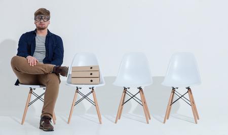 Ik ben klaar om een duik in de nieuwe onderneming. Vrolijke jonge man zit op een stoel en wachten op een sollicitatiegesprek. Hij is het dragen van een duikbril en kijken naar de camera serieus Stockfoto