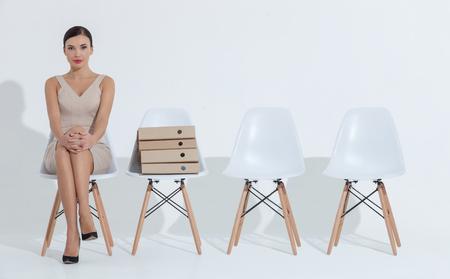 Je suis en attente pour un avenir réussi. jeune femme d'affaires élégant est assis sur une chaise près d'un tas de dossiers avec anticipation. Elle regarde la caméra avec confiance Banque d'images - 55380118