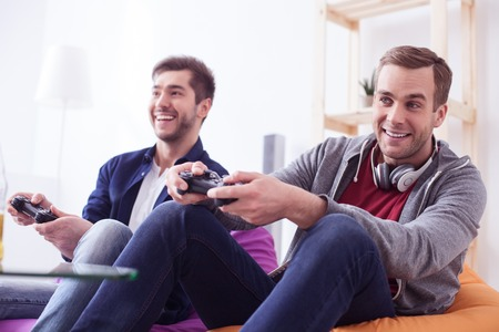 Handsome young friends are playing video game with joy. They are sitting on armchairs and laughing. The guys are looking forward with aspiration Stock fotó