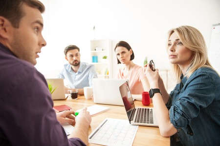 seriousness: Skillful young colleagues are arguing about the project. They are sitting at the desk in office. The man and woman are looking at each other with seriousness Stock Photo