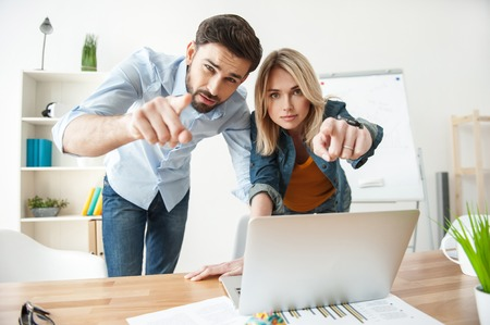 seriousness: Cheerful young colleagues are choosing something for their project. They are pointing finger forward with seriousness. The man and woman are standing near desk in office