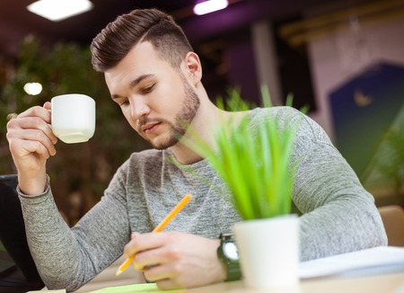 Cheerful male student is studying with concentration. He is sitting at desk and writing. The guy is drinking a cup of coffee Banco de Imagens