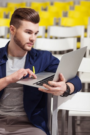 seriousness: Cheerful male student is studying at the university. He is sitting in lecture hall and using a laptop with seriousness Stock Photo