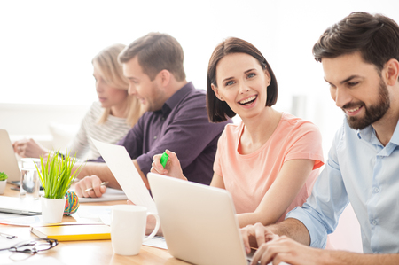 freelancers: Talented young freelancers are working in cooperation. They are sitting at desk and smiling. Man is typing on a laptop. Woman is looking at camera with happiness Stock Photo
