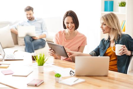 Joyeuses deux femmes se reposent au bureau après le travail. Ils sont assis au bureau et sourient. La femme tient une tablette. Son collègue pointe du doigt avec intérêt Banque d'images