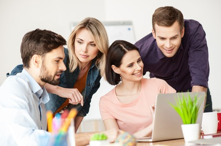 freelancers: Talented four freelancers are working with a laptop. The woman is sitting at desk and smiling. The man is standing near her with joy