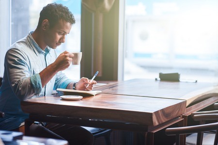 seriousness: Attractive young eastern guy is sitting at table in cafe. He is making notes into writing-pad with seriousness. The guy is drinking hot coffee Stock Photo