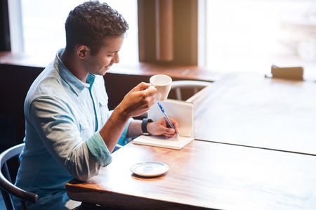 writing pad: Handsome eastern Arabian man is making notes into writing pad. He is sitting at desk in cafeteria. The man is holding a cup of coffee and smiling Stock Photo