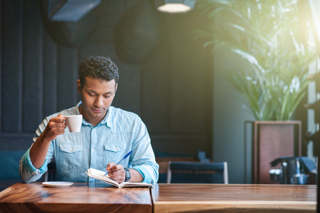 Attractive young man is writing his thoughts into notebook with inspiration. He is drinking coffee and sitting at table in cafe Stock Photo