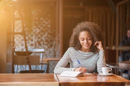 persona escribiendo: Atractiva chica africana está estudiando en la cafetería. Ella está haciendo notas y sonriendo Foto de archivo