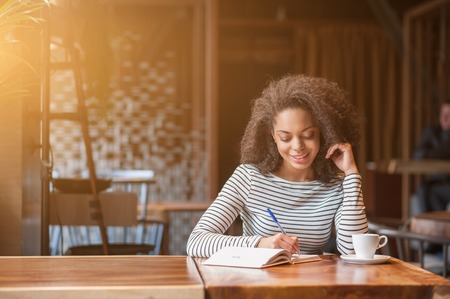 noting: Attractive african girl is studying in cafeteria. She is making notes and smiling Stock Photo