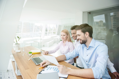 Skillful three colleagues are planning new project. They are watching presentation on laptop and sitting at desk. Man and woman are smiling with satisfaction Stock Photo
