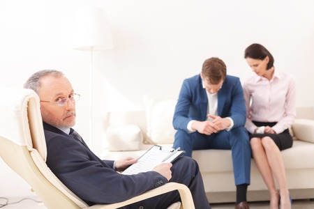 seriousness: Young family has problem is their marriage. The man and woman are sitting on sofa with desperation. The psychologist is looking at camera with seriousness