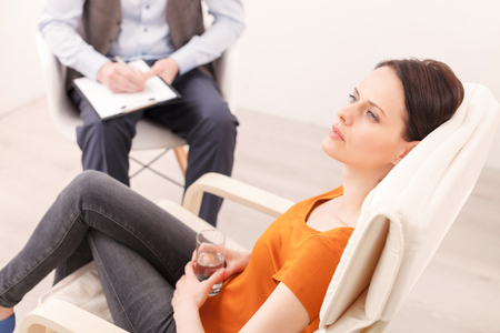 desperation: Pretty young girl is consulting a psychotherapist. She is sitting on chair and looking forward with desperation. The man is listening and writing