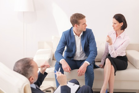 family practitioner: The doctor is right. Young family is solving their problems in psychotherapist. The woman is pointing finger at practitioner pensively. Her husband is looking at her seriously