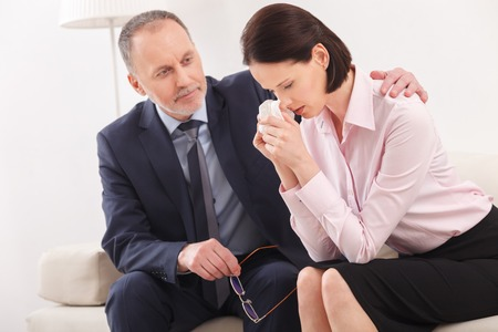 desperation: Cute young woman is crying with desperation in psychologist office. The mature doctor and supporting and embracing her with pity. They are sitting on couch