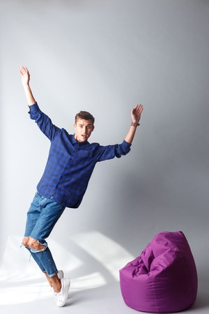 desilusion: retrato de cuerpo entero del hombre hermoso joven de pie y caer en la silla flexible. El levanta los brazos y mirando a la cámara con la decepción. Aislado Foto de archivo