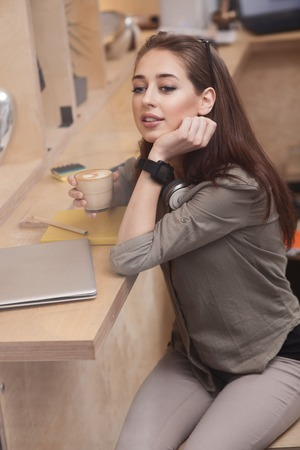 latter: Beautiful young woman is enjoying hot latter. She is dreaming and smiling. The lady is sitting at desk Stock Photo