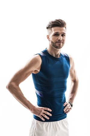 akimbo: I like sport. Waist up portrait of handsome strong athlete smiling and looking at camera happily. Man is standing with arms akimbo. Isolated