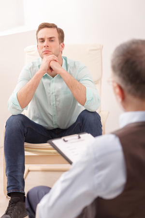 desperation: Young man is talking about his problems with a psychotherapist. He is sitting on chair and looking at doctor with desperation