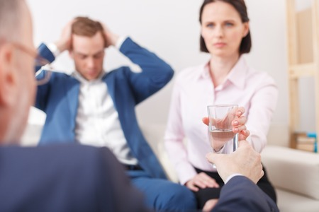 doctor giving glass: Young family is discussing their problems in psychologist. The man is sitting and touching his head with desperation. The doctor is giving a glass of water to woman. Focus on drink