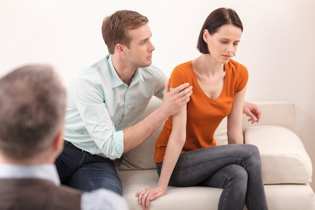 insult: Married couple is trying to solve their problems in psychologist office. The woman feels insult. The man is embracing her with love and apology Stock Photo
