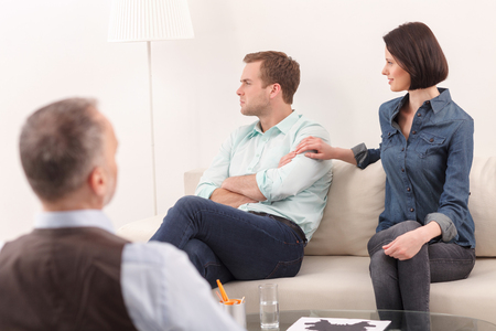 insult: Married family is sitting on couch in psychologist office. The man is looking aside with insult. His wife wants reconciliation. She is touching male shoulder and smiling