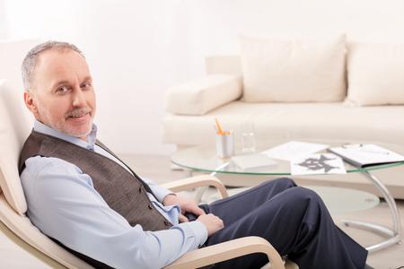 psicólogo profesional superior está sentado en una silla y sonriendo. Él está mirando a la cámara con alegría