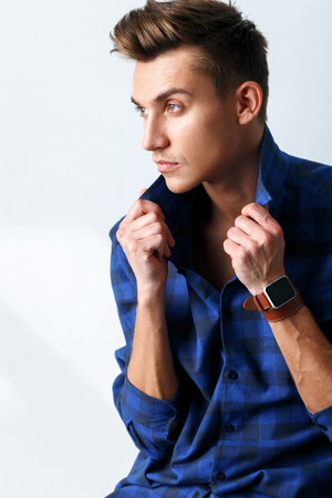 looking aside: Handsome man is sitting and looking aside seriously. He is touching collars of shirt. Isolated Stock Photo