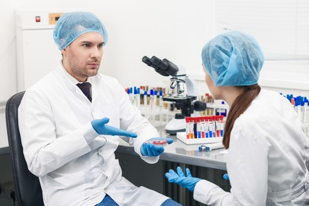 seriousness: Skillful two scientists are consulting about research. Man is holding a sample and pointing arm at it. He is sitting and looking at woman with seriousness