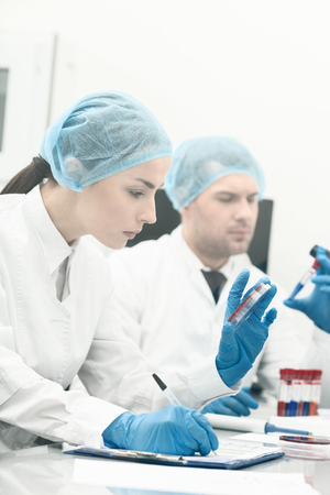 researchers: Professional young researchers are analyzing samples. Woman is making notes with seriousness. Man is holding a flask and looking at it pensively