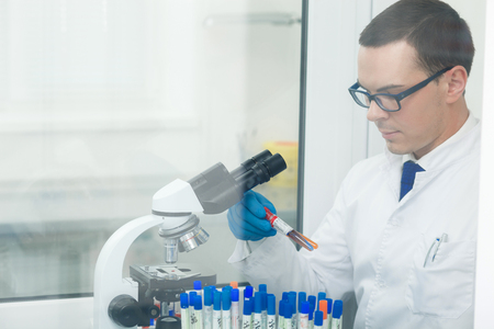seriousness: Cheerful male scientist is analyzing samples in lab. He is sitting at desk near a microscope. The man is holding flask and looking at it with seriousness Stock Photo