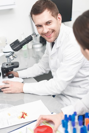 researchers: Skillful young researchers have successful results of work. The man is sitting at desk near a microscope and smiling. Woman is holding sample Stock Photo
