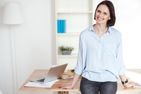 executive apartment: I like working at home. Portrait of beautiful young woman standing and leaning on the table with laptop and documents. She is looking at camera and smiling