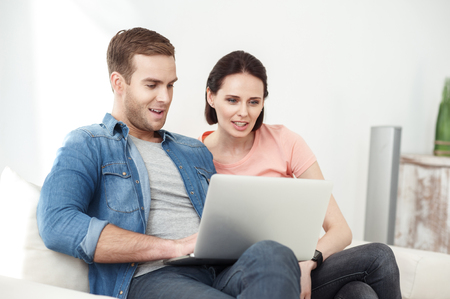 they are watching: Beautiful married couple is watching something on laptop. They are sitting on sofa and smiling