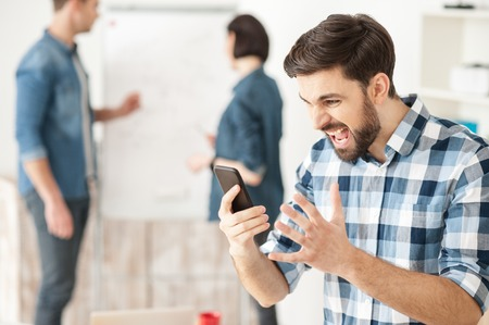 desperation: Attractive young man is holding a mobile phone and shouting at it with desperation. His colleagues are standing and discussing a project on background Stock Photo