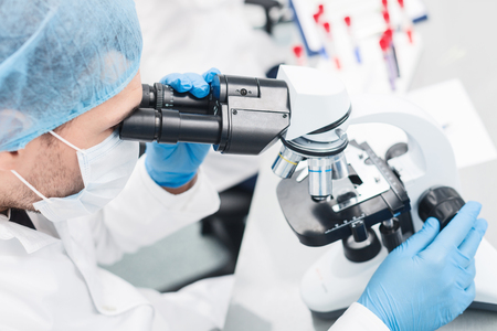 technologist: Professional young scientist is analyzing sample trough the microscope. The man is sitting with seriousness in laboratory
