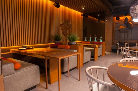 couches: Wonderful interior of modern restaurant. Wooden tables and small couches create cozy atmosphere
