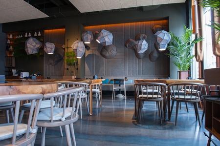 레스토랑에서 인테리어의 현대적인 디자인입니다. 의자가있는 우아한 테이블은 쾌적한 분위기를 연출합니다.
