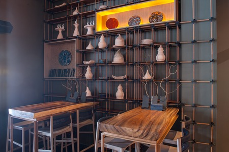 decoracion mesas: Elegant wooden tables and chairs in restaurant. Interesting utensil on the wall creates special decoration of interior