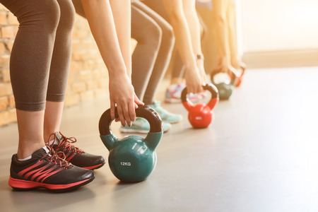 Close up of female arms lifting kettlebell in gym. Group of women are standing in row