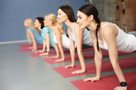美しい若い女性は、ジムで腕立て伏せをやっています。彼らは、trx トレーニングのストラップに足を傾いています。女性が笑っています。