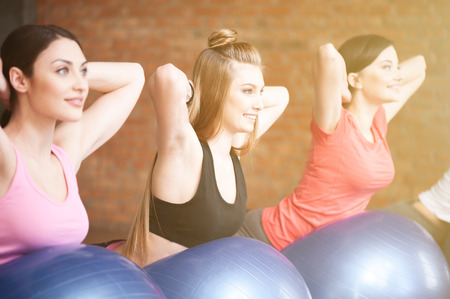 arms behind head: Attractive fit girls are exercising in group. They are lying on fitness ball and raising arms behind head. The ladies are looking forward with smile
