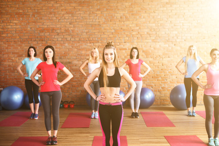akimbo: Attractive young women are doing exercise in gym. They are standing with arms akimbo. The ladies are smiling Stock Photo