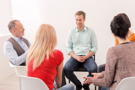 Attractive young man is sharing his feelings with psychologist and group. He is sitting and smiling. Women are listening with joy