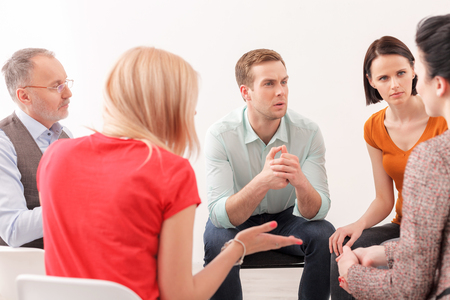 seriousness: Pretty young woman is telling about her problems to the group. They are listening to her attentively. The psychologist is sitting with seriousness