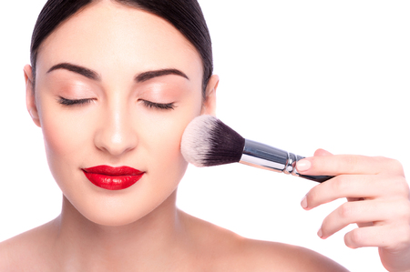 makeup eyes: Portrait of pretty girl doing make-up. Her eyes are closed with pleasure. Female hand of beautician is holding a brush and applying powder on her face. Isolated