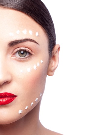 confidently: Close up of half of female face. Young woman is standing and looking forward confidently. Dots of cream are applied on her skin. Isolated Stock Photo