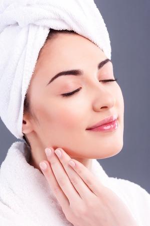 Retrato de mujer joven alegre es relajante en el spa. Ella está tocando su rostro suavemente y sonriendo. Sus ojos están cerrados de placer. La dama está de pie en bata de baño y toalla