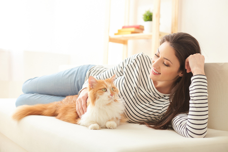 Beautiful young woman is resting with her small friend. She is lying on sofa and stroking a cat. The lady is smiling happily Stock Photo